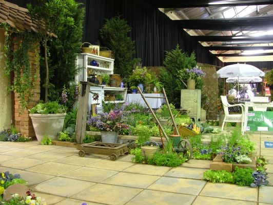 2006 Garden & Leisure show. Teracotta fish scale tiles, red brick columns, ivy and an array of old implements