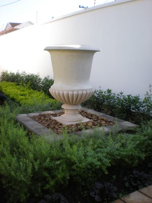 A Balmoral Pot in glass reinforced concrete in a newly planted garden