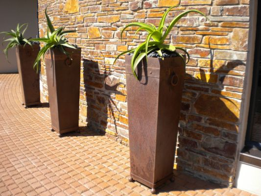 Rusted Arabic pots with ball feet and handle detail are filled with black pebbles and planted with Aloe van balenii