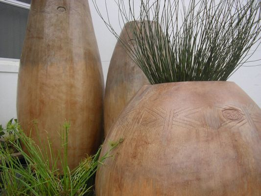 Three ethnic pots - the one in front planted with a Chondropetalum tectorum