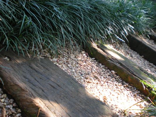 1m wooden railway sleepers with Duzi gravel between, edged with Ophiopogon japonicus