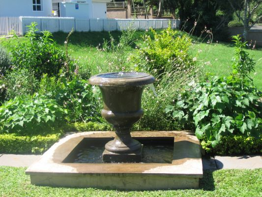 A concrete Victorian urn in a raised pond in a small English inspired garden