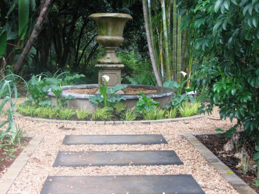 A raised pond with central Victorian urn on a plinth is a feature in this tropical garden