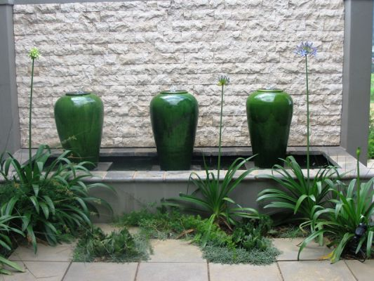 A trio of glazed Ceramic jars in a striking jade green are complimented by Agapanthus, Asparagus and Juncus