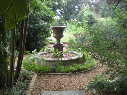 A Victorian urn in a raised pond is a striking addition to this cool, serene section of this garden