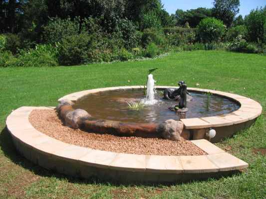 This circular pond with rim flow detail was designed to fit this lawn area with a gentle slope