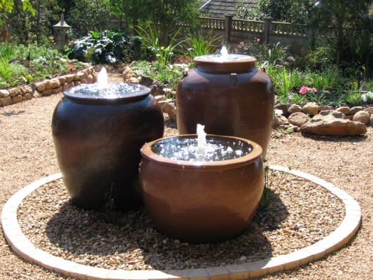 This trio of overburnt black clay pots is a dominant feature of this small town house garden
