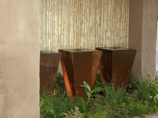 A trio of rust techniqued fibrecrete pots complimented with nTingu screens and indigenous planting