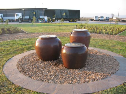 Overburnt black clay pots catch the late afternoon sun in this corporate garden