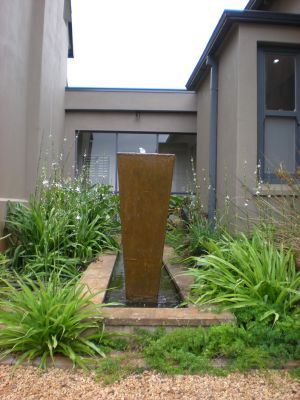 This long narrow raised water feature has three tall concrete pots and is surrounded with Chlorophytum bowkerii